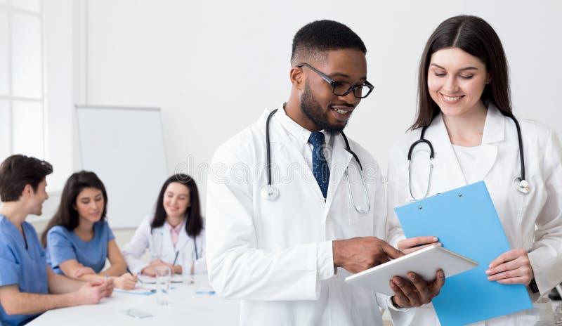 Unga doktorer som använder den digitala minnestavlan som diskuterar diagnos arkivfoto