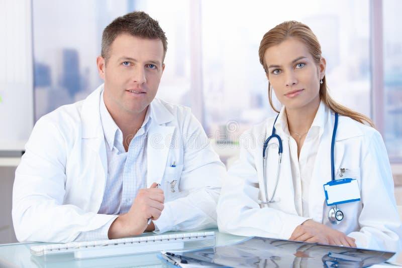 Unga doktorer som sitter på att konsultera för skrivbord fotografering för bildbyråer