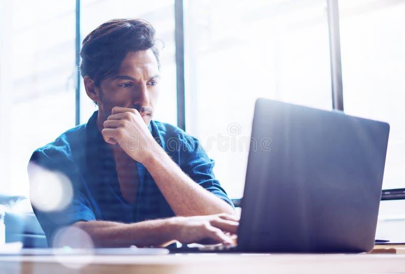 Unga eleganta bankrörelsen finansierar analytikeren som arbetar på det soliga kontoret på bärbara datorn, medan sitta på trätabel royaltyfri foto