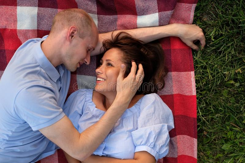 Unga europeiska par som lägger på gräset som ser på de arkivfoton