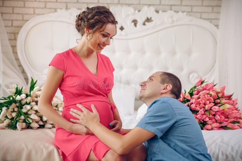 Unga föräldrar i säng som lite förväntar, behandla som ett barn, romantiska ögonblick för gravida par arkivbilder