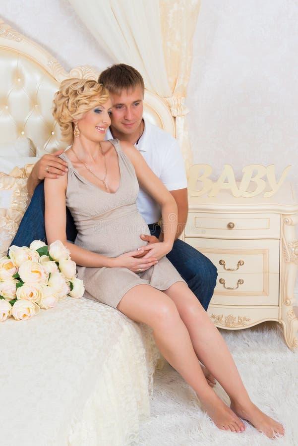 Unga föräldrar i säng som lite förväntar, behandla som ett barn, romantiska ögonblick för gravida par royaltyfri bild