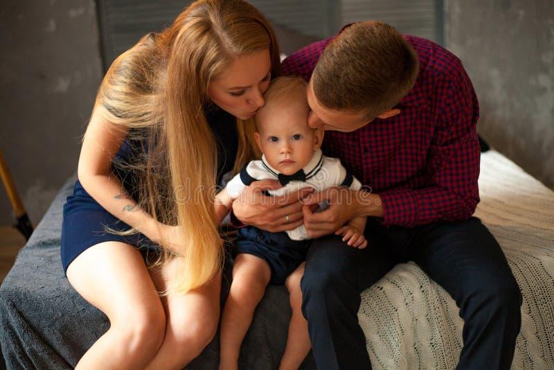 Unga föräldrar kysser deras lilla son royaltyfria bilder