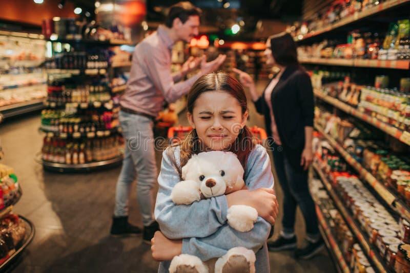 Unga föräldrar och dotter i livsmedelsbutik Hon sitter i spårvagn- och omfamningleksakbjörn Flickan håller ögon stängda Förälderh royaltyfri foto