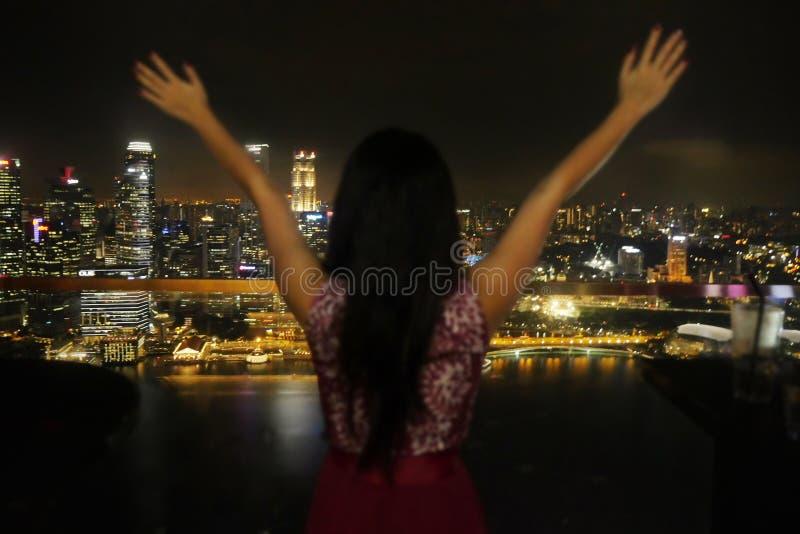 Unga fördelande armar för elegant kvinna fritt däckar överst takstången framme av den fantastiska härliga sikten av stadsljus på  arkivbild