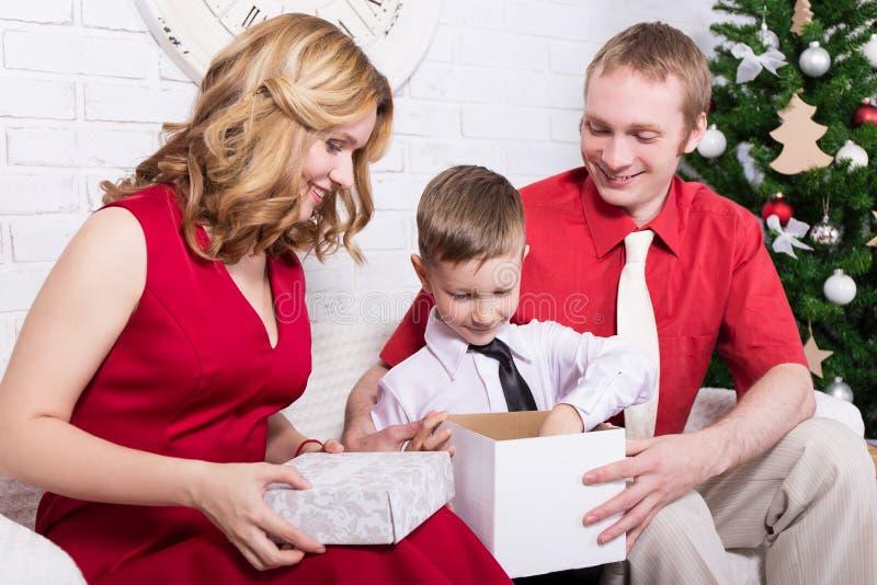 Unga familjöppningsgåvor framme av julgranen arkivfoto