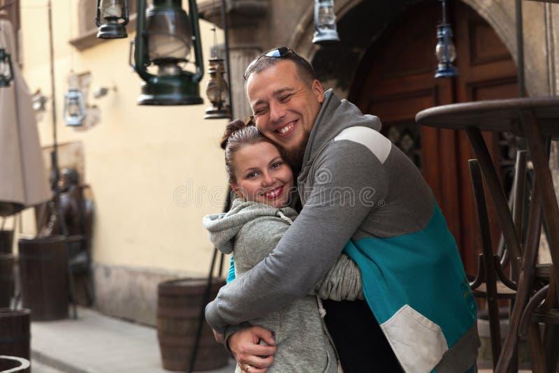 Unga familjpar har en gyckel på mötet på den gamla antika stadsgatan Romantiska par som tycker om i ögonblick av lycka royaltyfri fotografi