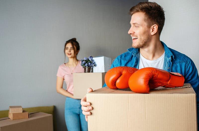 Unga familjpar köpte eller hyrde deras första lilla lägenhet Grabbställning framme och kvinna på tillbaka De rymmer askar fotografering för bildbyråer