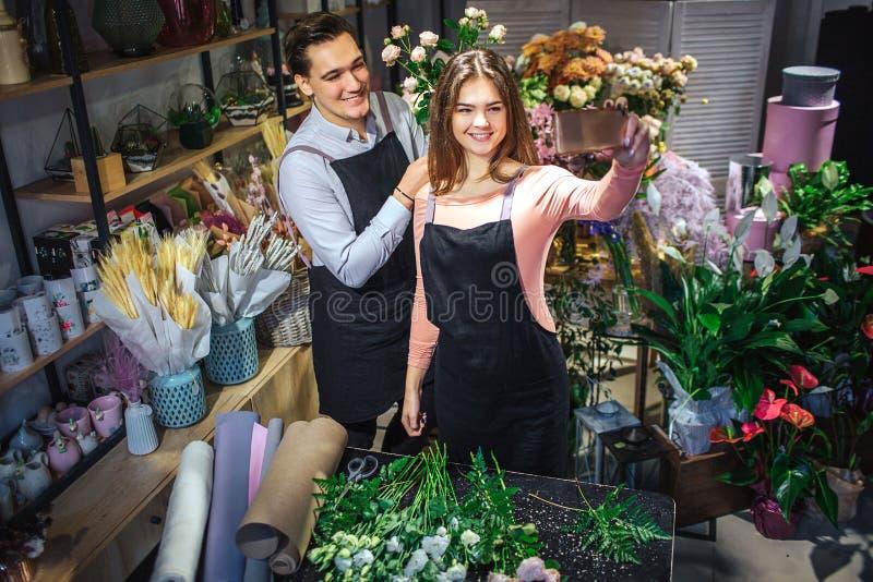 Unga femal och manliga blomsterhandlare står i rum som är fullt av blommor och växter Hon rymmer honen De tar selfie Folkleende royaltyfria foton