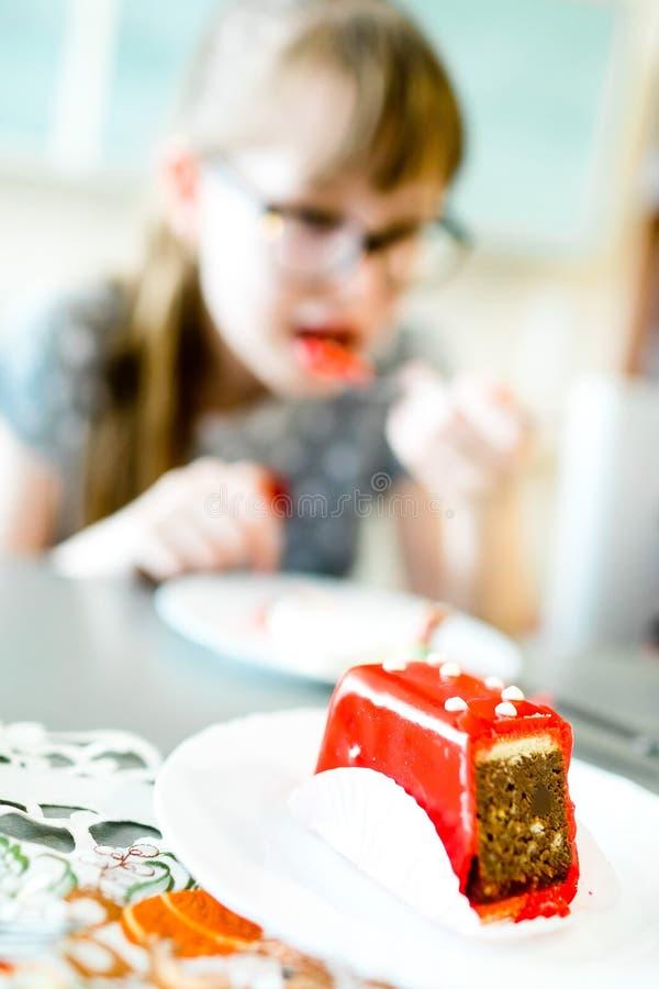 Unga flickan äter den röda kakan med vita prickar arkivbilder