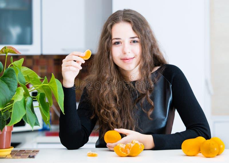 Unga flickan äter en apelsin arkivfoton