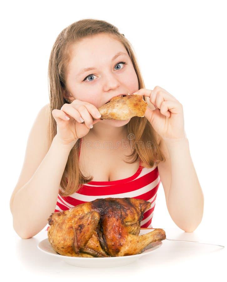 Unga flickan äter greedily ett stycke av höna royaltyfri fotografi
