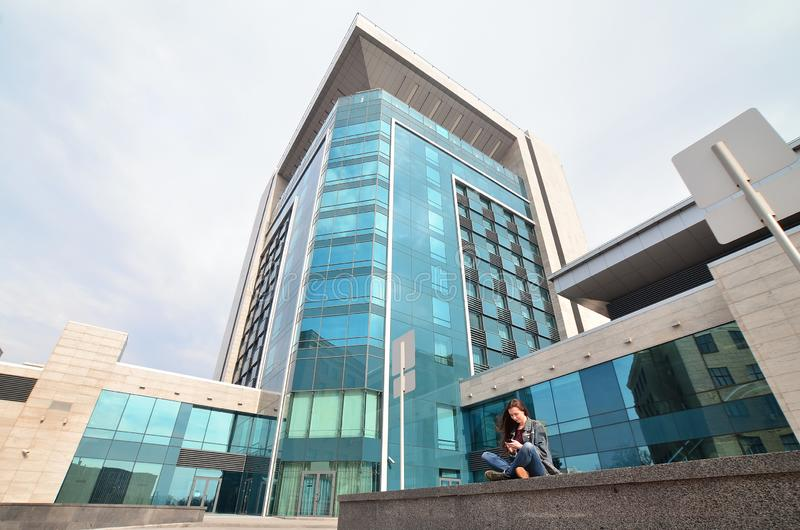Unga flickan använder en smartphone på kontorsbyggnadbakgrunden royaltyfri foto