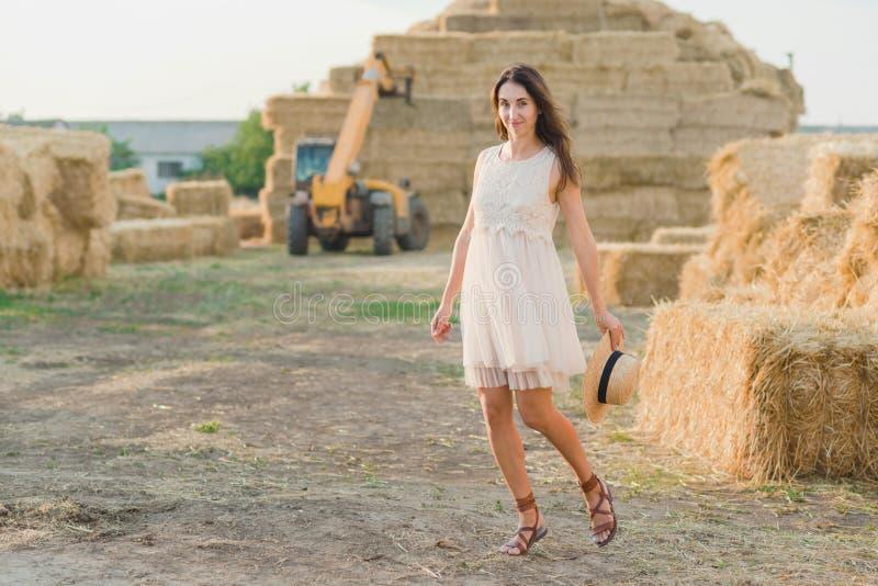 Unga flickan bär den vita klänningen för sommar nära höbalen i fält Härlig flicka på lantgårdland Gul guld- skörd för vete i höst royaltyfri foto