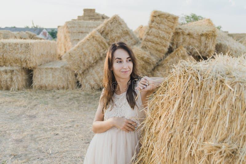 Unga flickan bär den vita klänningen för sommar nära höbalen i fält Härlig flicka på lantgårdland Gul guld- skörd för vete i höst royaltyfria foton