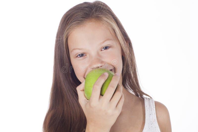 Unga flickan biter ett grönt äpple arkivbild