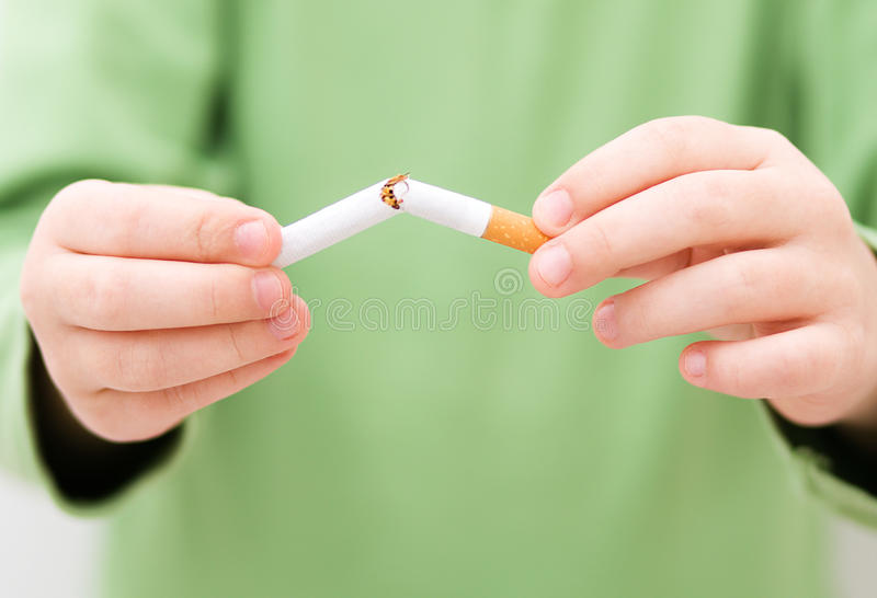 Unga flickan bryter en cigarett arkivfoto