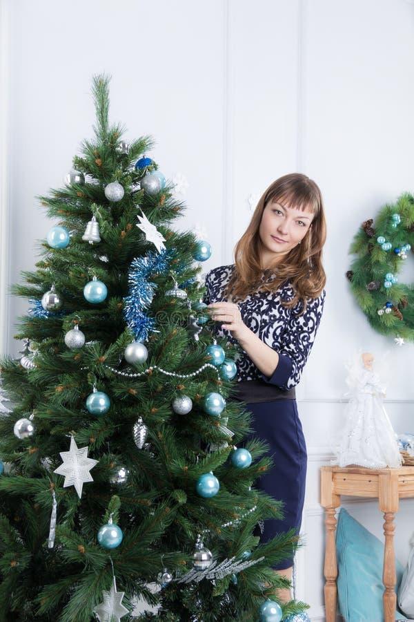 Unga flickan dekorerar julgranen royaltyfria foton