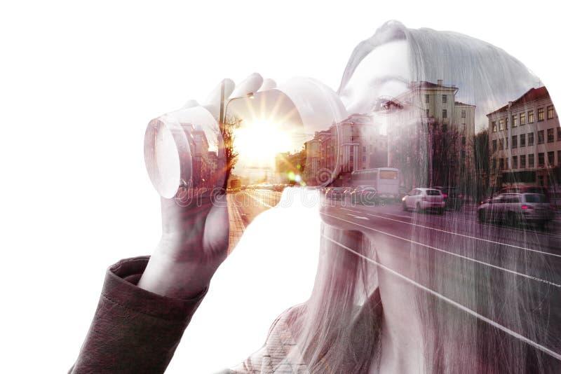 Unga flickan dricker kaffe på bakgrunden av staden arkivfoto