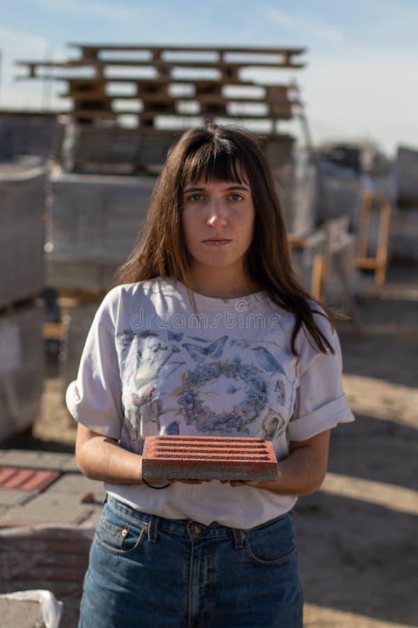 Unga flickan fäster en golvtegelplatta på en industriell plats royaltyfri bild