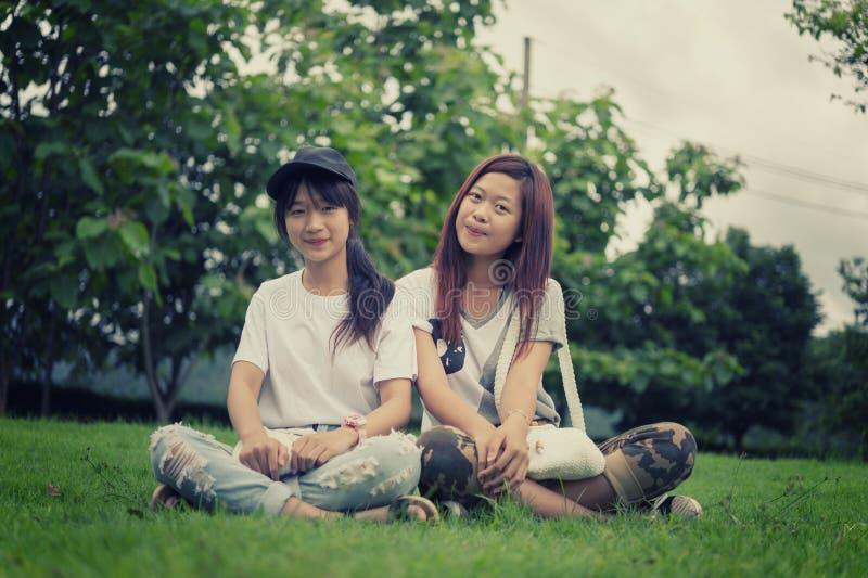 Unga flickan för två asia med påsen parkerar på arkivfoto