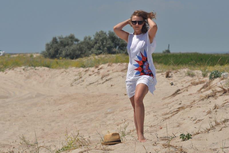 Unga flickan går barfota på sanden royaltyfria foton