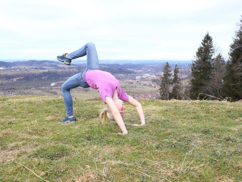 Unga flickan gör en sportövning royaltyfria bilder