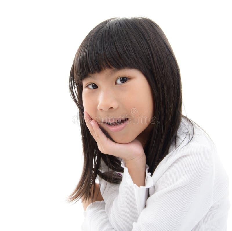 unga flickan grinar med hennes haka i henne händer arkivbild