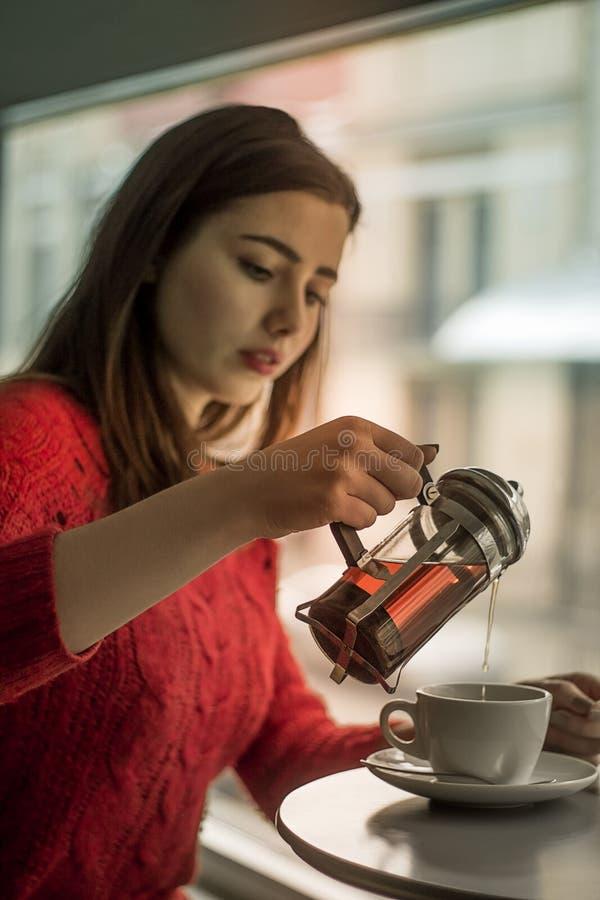 Unga flickan häller svart te från den glass kokkärlet till den smal koppen arkivfoton