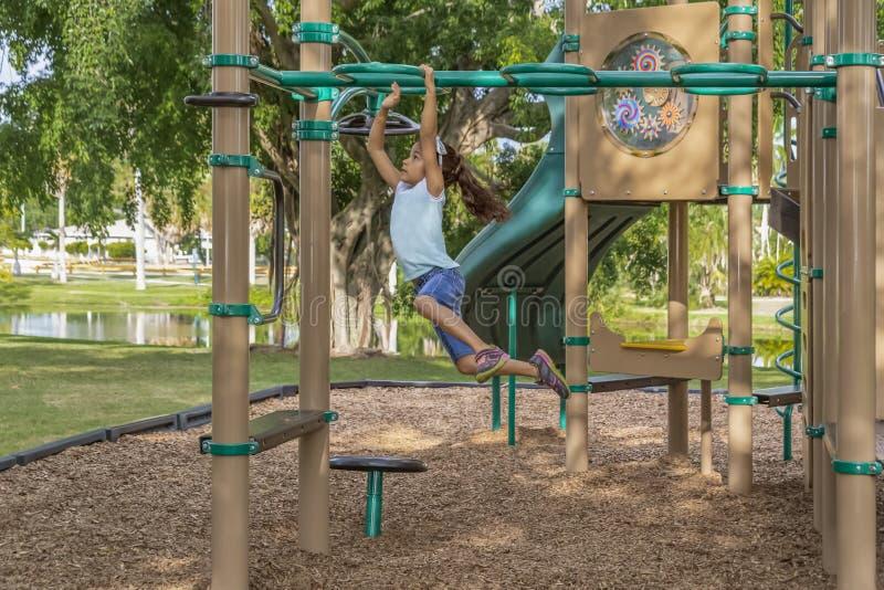 Unga flickan hoppar och svänger över stängerna på den utomhus- klätterställningen royaltyfri fotografi