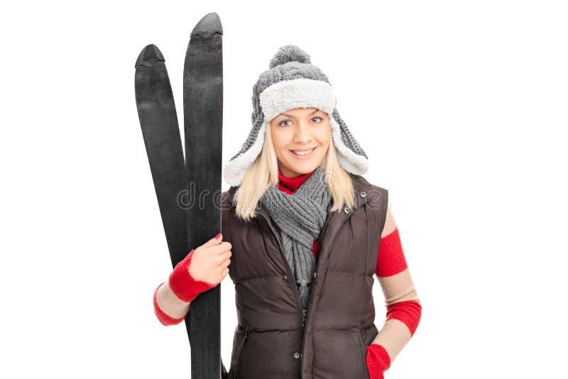 Unga flickan, i att rymma för vinterkläder, skidar royaltyfria foton