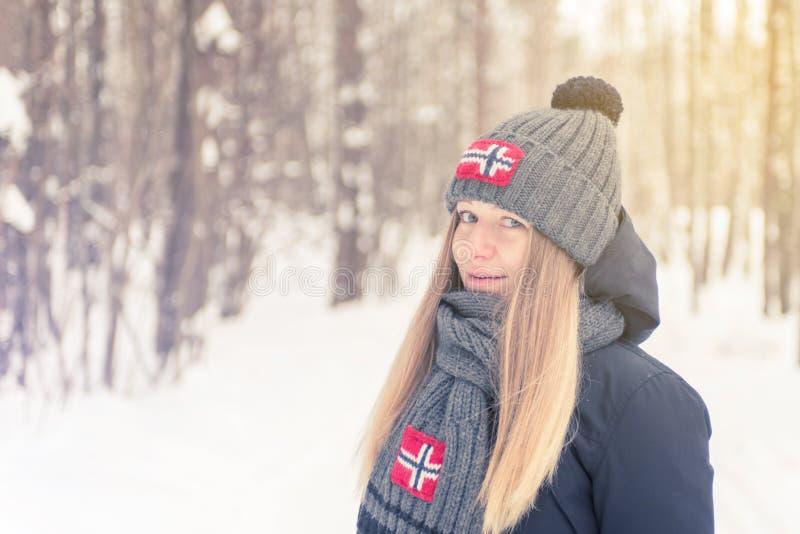 Unga flickan i det kalla trät för vinter i ett lock och en halsduk med arkivfoto