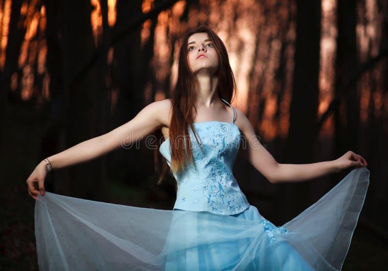 Unga flickan i en lång blått klär dans i den mörka skogen fotografering för bildbyråer