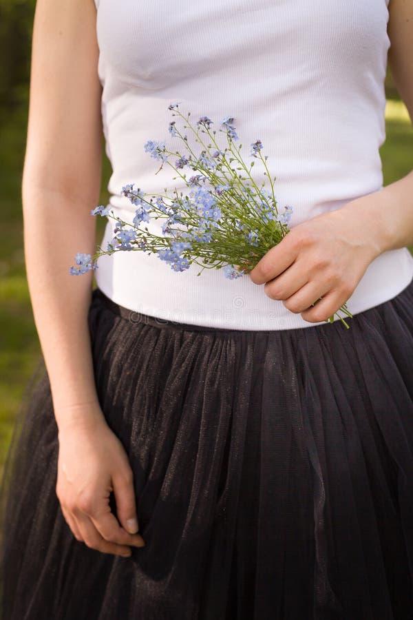 Unga flickan i en vit ärmlös tröja och den svarta fluffiga kjolen som rymmer en härlig bukett av, glömmer mig inte blommor i henn arkivfoto