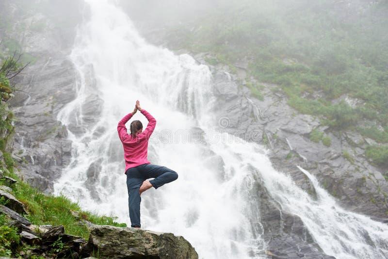 Unga flickan i en yoga poserar nära den kraftiga vattenfallet fotografering för bildbyråer