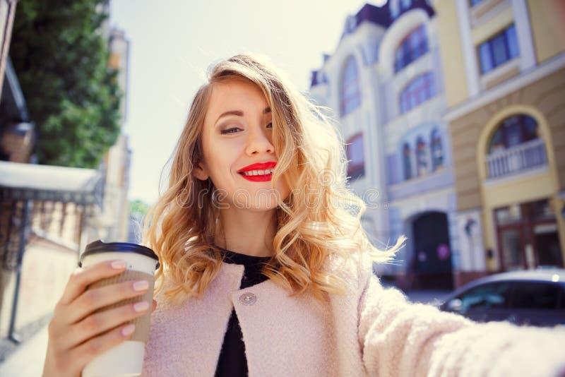 Unga flickan i ett exponeringsglas av kaffe i hennes hand gör selfie på royaltyfri foto