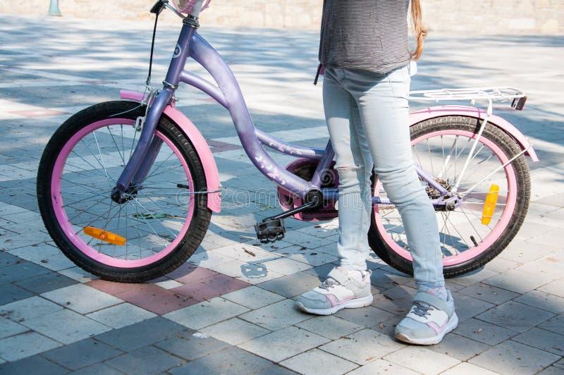 Unga flickan i grov bomullstvillflåsanden står nära cykeln som rymmer det fotografering för bildbyråer