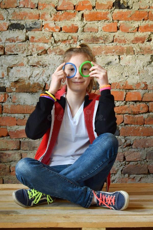 Unga flickan i jeans och den vita T-tr?ja sitter p? golvet och le Begreppsst?ende av en angen?m v?nlig lycklig ton?ring royaltyfri bild