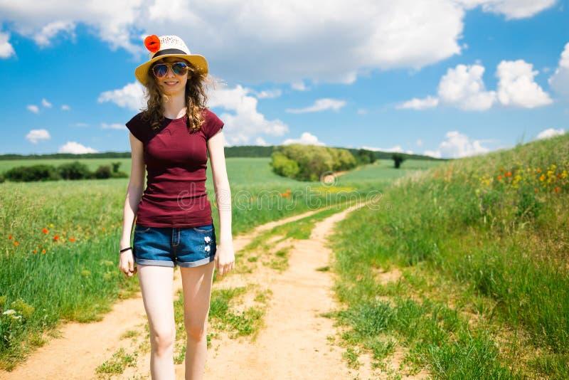 Unga flickan i kort jeans och vallmoblomma i hatt går på royaltyfri foto