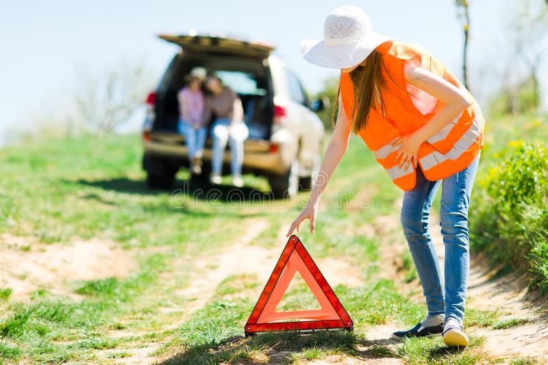 Unga flickan i orange triangel för västaktiveringssammanbrott står nära en bruten bil royaltyfria bilder