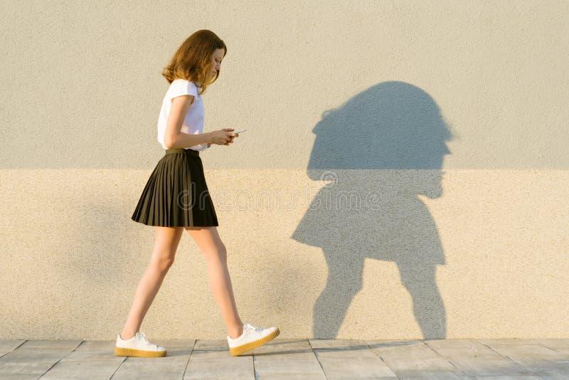 Unga flickan i profilen, promenerar den gråa väggen, i händerna av mobiltelefonen Utomhus- kopieringsutrymme royaltyfri fotografi