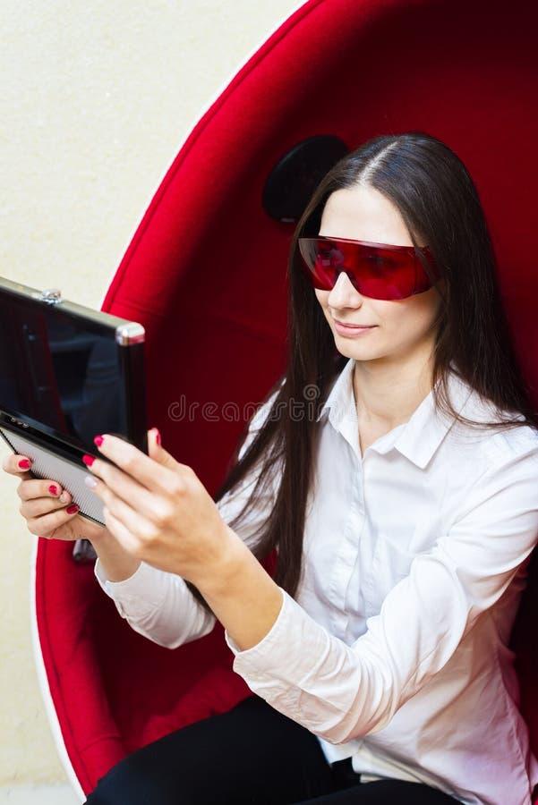 Unga flickan i röda exponeringsglas ser i spegeln Kvinna som sitter i en r?d stol royaltyfria foton