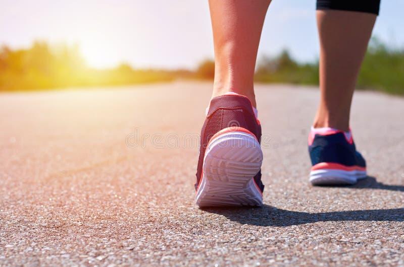 Unga flickan i rinnande skor kör längs vägen, henne endast som, är ben synliga, ben och gymnastikskor, solljus fotografering för bildbyråer