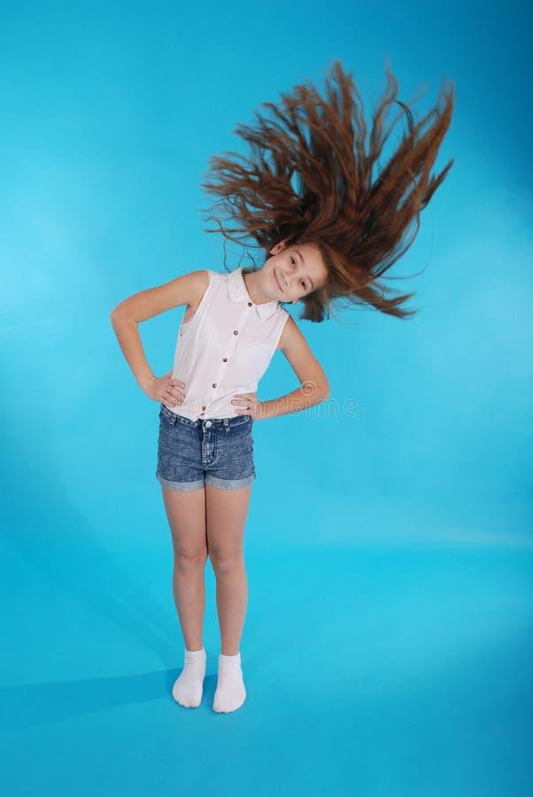 Unga flickan kastar upp hennes hår royaltyfri foto