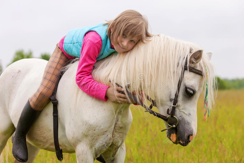 Unga flickan ligger på baksidan för den vita hästen arkivbild
