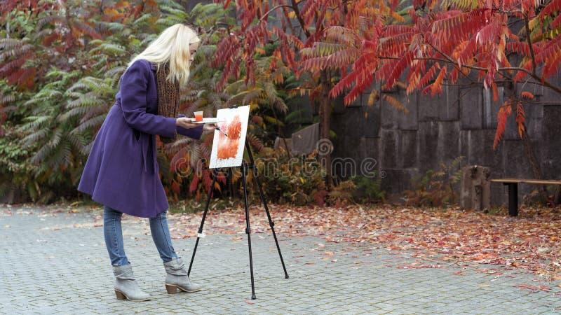 Unga flickan målar en bild i hösten parkerar arkivbilder