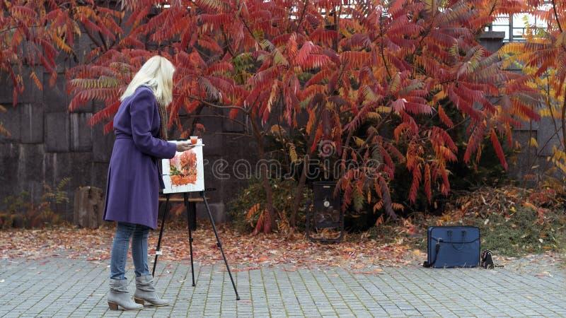 Unga flickan målar en bild i hösten parkerar arkivbild
