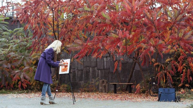 Unga flickan målar en bild i hösten parkerar arkivfoton