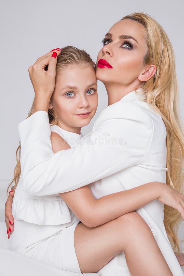 Unga flickan med den härliga dottern av fantastiska blåa ögon och röda kanter och spikar mamman som tätt blont lockigt hår sitter fotografering för bildbyråer