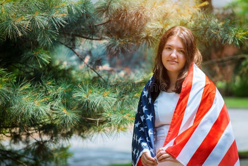 Unga flickan med den klassiska kl?nningen som rymmer amerikanska flaggan i, parkerar sj?lvst?ndighetsdagen arkivbild